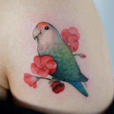 Lovebird tattoo by Tattoist Doy #TattooistDoy #naturetattoos #color #realism #realistic #watercolor #fineline #lovebird #bird #feathers #wings #flowers #pink #floral #leaves #tattoooftheday