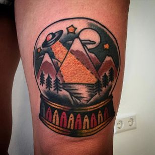 UFO in the mountains in a snow globe tattoo by Augusto Rodriguez. #snowglobe #glass #UFO #mountain #traditional