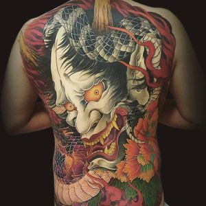 The Oni rears his head by Hajin Irezumi #HajinIrezumi #japanese #newtraditional #mashup #color #Onimask #oni #snake #leaves #fire #smoke #fangs #scales #backpiece #tattoooftheday