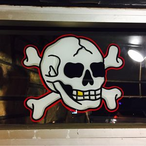 A skull and crossbones painted by Tina Fino on Bound for Glory's window (IG—tina_fino). #BoundforGlory #signpainting #tattooinspired #skullandcrossbones #TinaFino