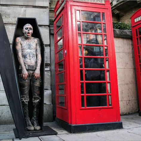Awesome shot by Casey Gutteridge of Zombie Boy in a coffin next to a phone booth. #heavilytattooed #model #photography #RickGenest #ZombieBoy
