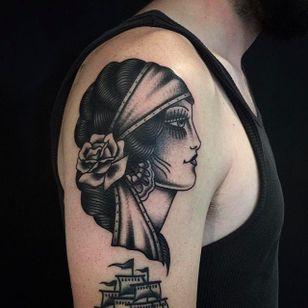 An elegant looking black gypsy head tattoo by Anem. #Anem #traditionaltattoo #girl #girltattoo #blackwork #traditional #traditionalgirl #gypsy