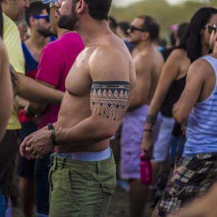 Festival fan showing off his geometric armband tattoo, photo by Rodrigo Zaim and Lucas Jacinto #tomorrowlandbrazil #festival #tattoostyle #RodrigoZaim #LucasJacinto #blackwork