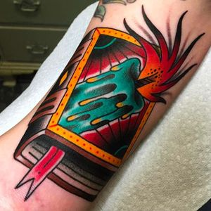 Beautiful book and candle tattoo by Tom Lortie. #TomLortie #traditionaltattoo #coloredtattoo #book #candle