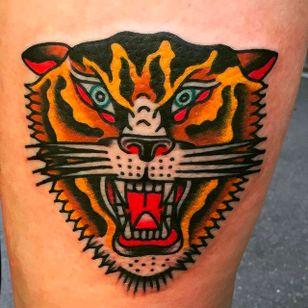 Solid and vibrant tiger head tattoo done by Alex Wild. #AlexWild #traditionaltattoo #boldtattoos #tigerhead #tiger #growlingtiger