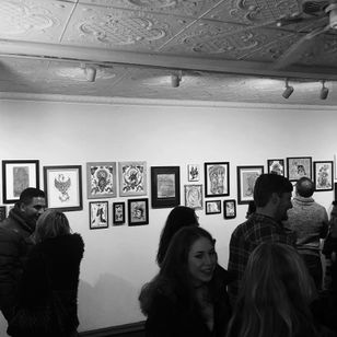 Partygoers take in the art show at Eight of Swords. Photo by Katie Vidan