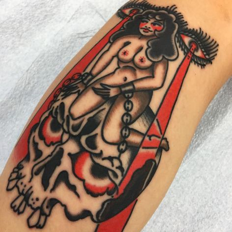A dark pinup chained to a skull by Thomas Leyh (IG—thomasleyh). #NYCtattooshops #pinup #RedRocketTattoo #skull #ThomasLeyh #traditional