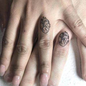 Matching tattoos by Anna Neudecker #AnnaNeudecker #hearttattoos #linework #coupletattoo #matchingtattoo #anatomicalheart #marriagetattoo #ringtattoo #heart #love #marriage #couple #small #minimal