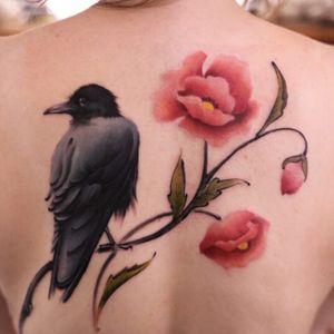 Raven tattoo with poppy flowers #raven #crow #flowers #watercolor #redflowers #poppies #raventattoo #feminine #back #backpiece #birdandflowers #bird #poppy